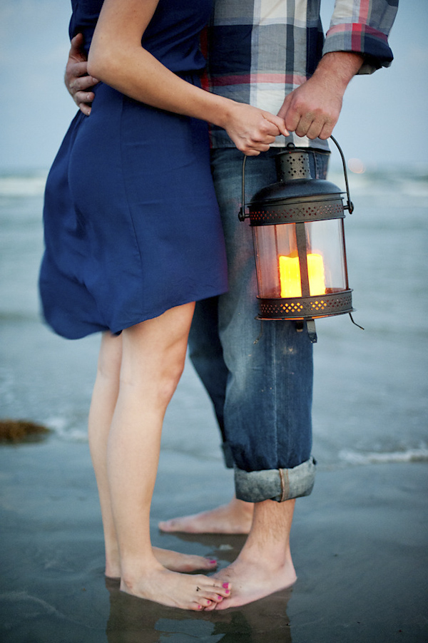 closeup perspective of the happy couple standing on beach with lantern - romantic waterfront engagement session - photo by Houston based destination wedding photographer Adam Nyholt