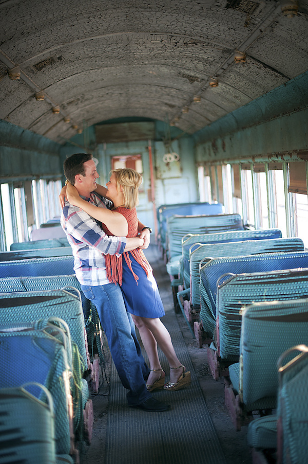 happy bride-to-be leaning into groom - vintage train car engagement shoot - photo by Houston based destination wedding photographer Adam Nyholt