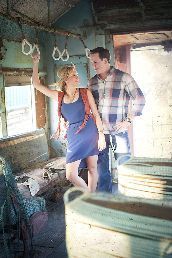 stylish couple posed in vintage train car - playful engagement photo by Houston based destination wedding photographer Adam Nyholt