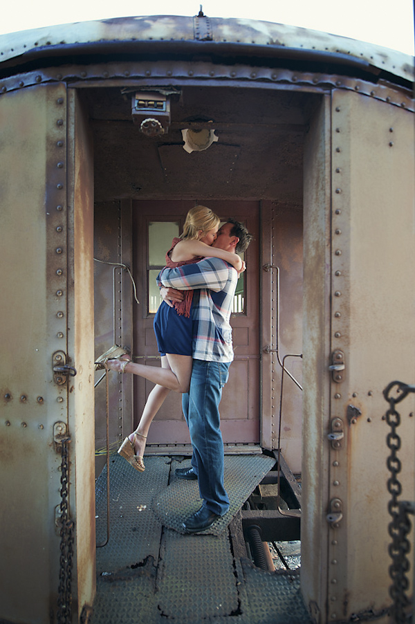 the happy couple kissing romantically on vintage train car - creative engagement photo by Houston based destination wedding photographer Adam Nyholt