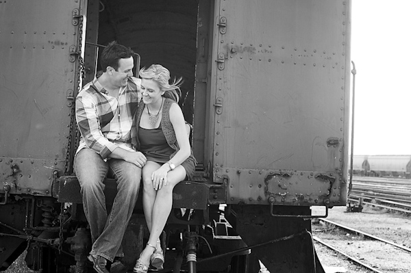 black and white photo of the happy couple laughing together on back of antique train car - engagement session by Houston based destination wedding photographer Adam Nyholt