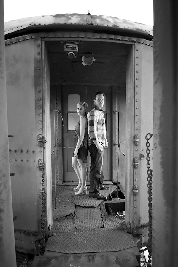 black and white photo of bride and groom-to-be standing back to back on vintage train car - engagement photo by Houston based destination wedding photographer Adam Nyholt