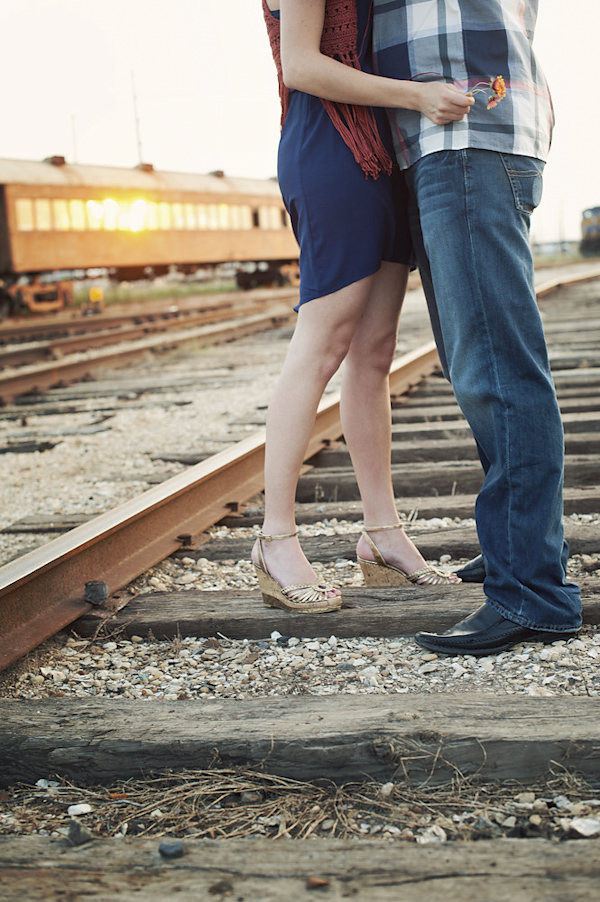 cropped perspective of the happy couple's feet while hugging - creative engagement session in empty train yard - photo by Houston based destination wedding photographer Adam Nyholt
