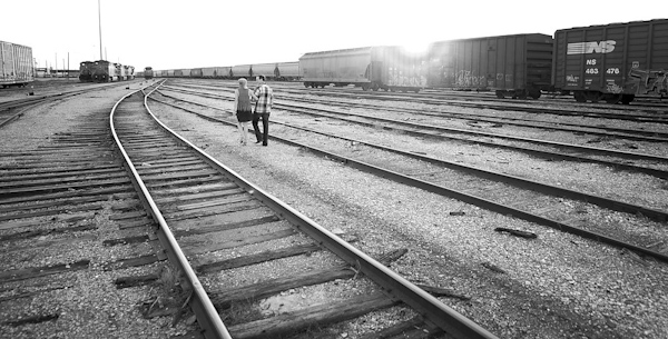 wide angle, black and white photo of the happy couple walking in empty train yard - photo by Houston based destination wedding photographer Adam Nyholt