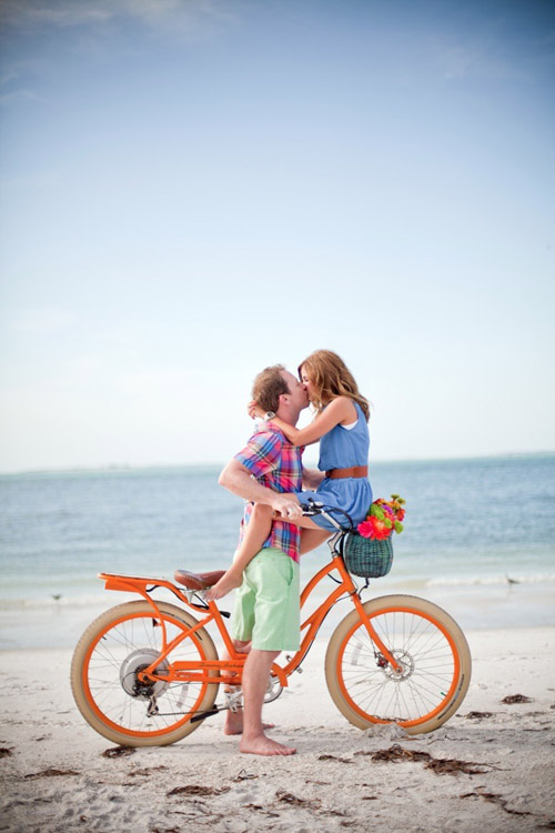summer engagement photo on the beach with an orange bicycle by Slaton Weddings | via junebugweddings.com