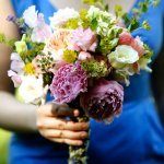 bridesmaid in blue holds assorted bouquet - charming Hudson Valley NY wedding photo by top New York wedding photographers Belathee Photography