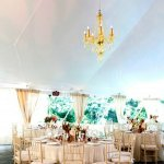 round table seating in a tented reception area - gold chandelier - charming Hudson Valley NY wedding photo by top New York wedding photographers Belathee Photography