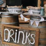 Reception decor with rustic barrels as drink table - wedding photo by Michigan-based wedding photographers Bryan and Mae