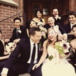 the happy couple surrounded by guests and sitting on stairs - wedding photo by top Orange County, California wedding photographers D. Park Photography