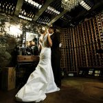 the newlywed standing in wine cellar - wedding photo by top Orange County, California wedding photographers D. Park Photography