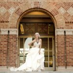 dramatic bride posing in front of school building - wedding photo by top Orange County, California wedding photographers D. Park Photography