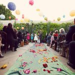 colorful paper lanterns and colorful flower petals decorate an outdoor ceremony site- vintage LA wedding at The Smog Shoppe photo by top Orange County wedding photographer Duke Images