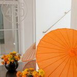 Bright orange umbrella and floral decor at modern and colorful New York City loft wedding | Photo by Image Singuli�re