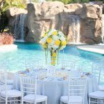 Tall yellow and white centerpiece at a beautiful poolside wedding reception - Photo by April Smith & Co.