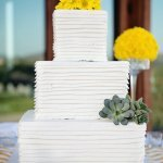 Stunning square, 3-tiered wedding cake with yellow flowers and succulents - Photo by April Smith & Co.