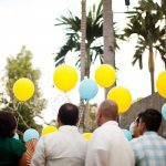guests hold yellow and blue balloons to release - traditional Indonesian wedding in Bali - photo by Portland wedding photographer Bunn Salarzon