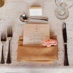 Wedding menu tucked in tan napkin with pink flower detail - Photo by Sara and Rocky Photography