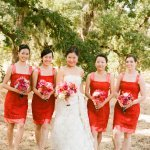 Beautiful bride with bridesmaids wearing short, bright red dresses - Photo by Sylvie Gil Photography