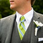 groom in gray suit with chartreuse and blue tie - white and light blue boutonniere -  preppy New York Sagamore resort wedding photo by New York wedding photographer Tracey Buyce