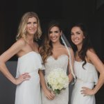 Beautiful bride wearing ivory while her bridesmaids wear white - Photo by Whitewall Photography