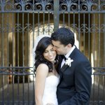 Groom kisses his bride in front of a beautiful iron gate- wedding photo by top Canadian wedding photographer Rebecca Wood