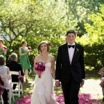 Couple exiting ceremony on an outdoor aisle of dark pink and purple petals - photo by top Atlanta-based wedding photographer Scott Hopkins Photography