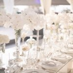white orchid floral arrangements and place settings on long table at wedding reception, photo by Melissa Jill Photography