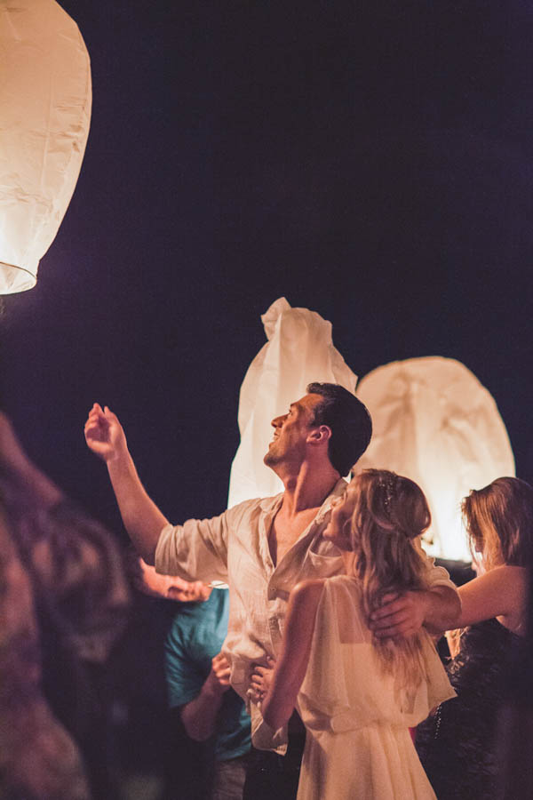 intimate beach wedding reception with floating lanterns, photo by Chris Glenn | via junebugweddings.com
