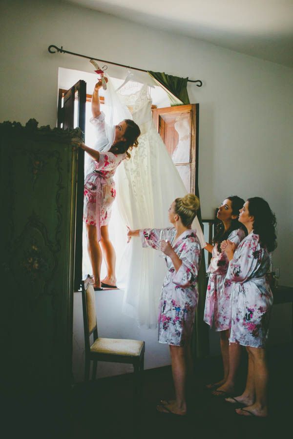 bride and bridesmaids getting the dress