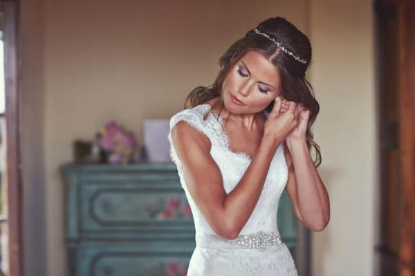 beautiful bride putting on earrings
