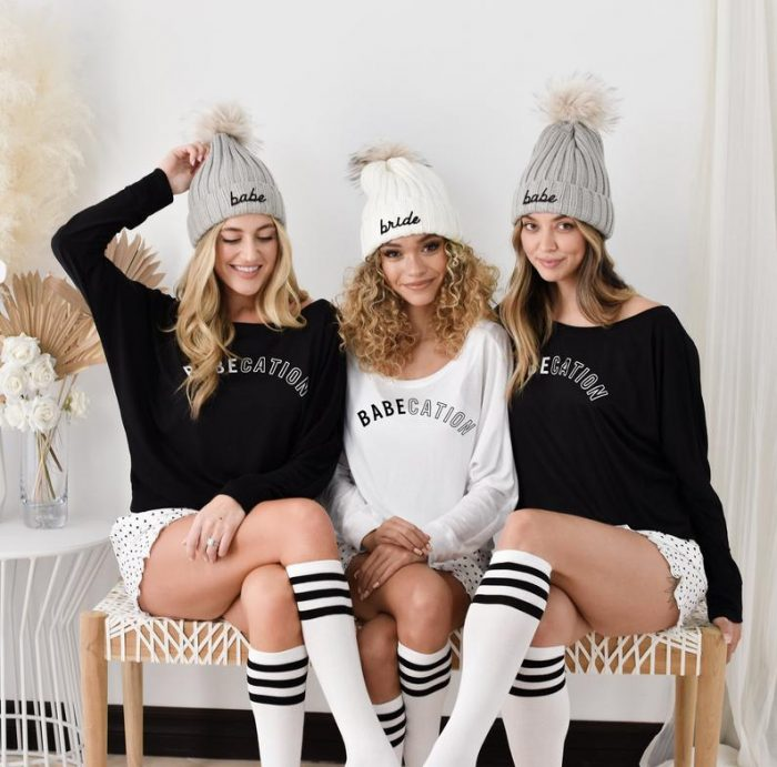 three women wearing beanies