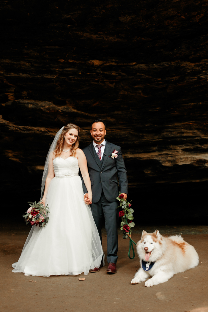 bride and groom posing together with puppy