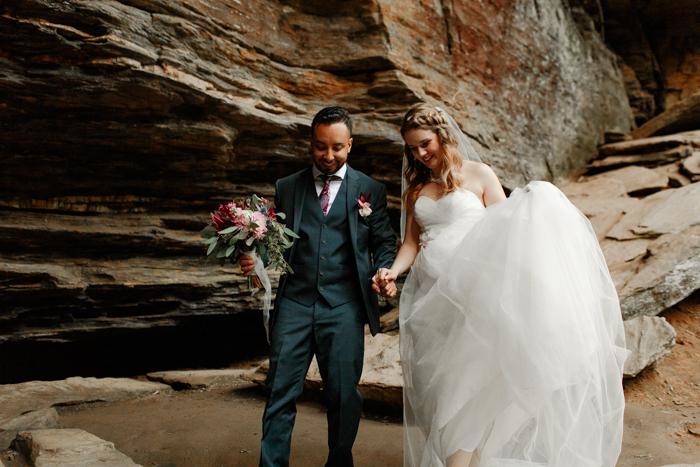 groom helping bride hike